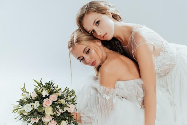 花束のバラとウェディングドレスでポーズをとる2つの若い美しい花嫁 Premium写真