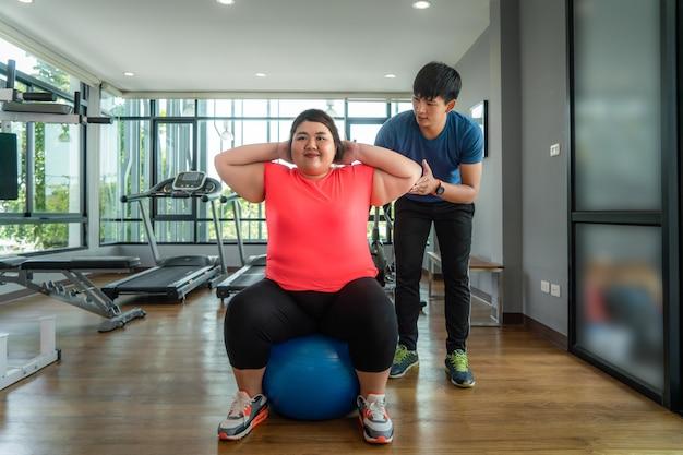 2つのアジアのトレーナーの男と太りすぎの女性が一緒にモダンなジムでボール運動、幸せとトレーニング中に笑顔します。太った女性は健康を大事にし、体重を減らしたいと考えています。 Premium写真