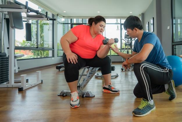 2つのアジアのトレーナーの男と太りすぎの女性が一緒にモダンなジムでダンベル運動、幸せとトレーニング中に笑顔。太った女性は健康を大事にし、体重を減らしたいと考えています。 Premium写真