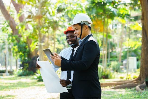 アジアとアフリカの建築家エンジニア2つの専門チームが緑の自然の中で笑顔で計画します。 Premium写真