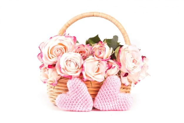 枝編み細工品バスケットの美しいピンクのバラと白地に2つのニットピンクハート。 Premium写真