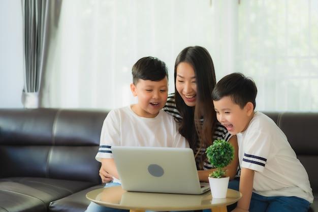 2彼女の息子を持つ美しい若いアジア女性ママはソファーでラップトップまたはコンピューターのノートブックを使用します 無料写真