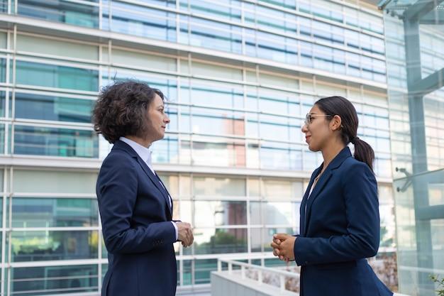 オフィス近くのプロジェクトを議論する2人のビジネス女性 無料写真