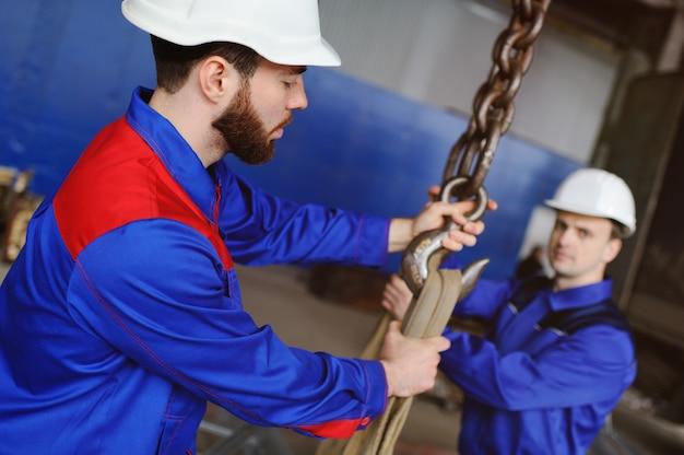 2人の労働者がクレーンフックに工業製品を積み込む Premium写真