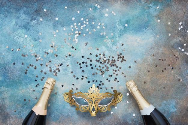 2つのシャンパンボトル、ゴールデンカーニバルマスクと青い背景に紙吹雪星。 Premium写真