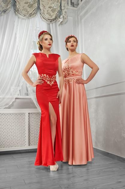 長い夜の赤と桃のドレスの2人の若い美しい女性 無料写真
