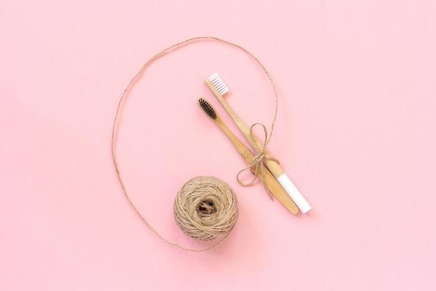 ピンク色の背景にひもで結ばれた白と黒の剛毛を持つ2つの自然環境に優しい竹のブラシ Premium写真