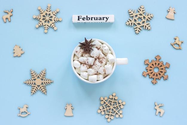 カレンダー2月マグカップココアマシュマロと大きな木製の雪片 Premium写真