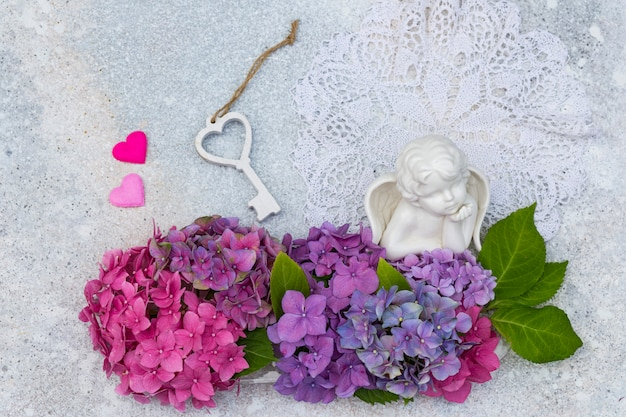 アジサイの花束、陶器製の天使、2つのハート、木製の鍵 Premium写真