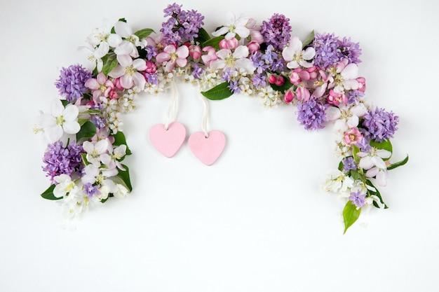 アーチと2つのピンクのハートが並ぶ鳥の桜、ライラック、りんごの木の花 Premium写真