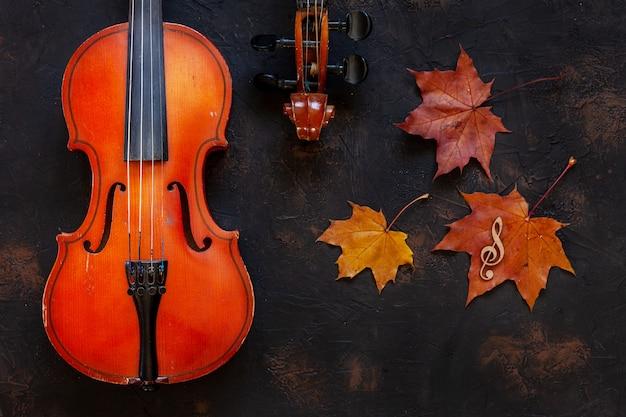 Старая скрипка 2 с желтым кленовым листом осени. Premium Фотографии