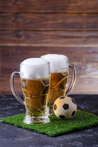 ビール2杯、緑の芝生にサッカーボールの写真 Premium写真