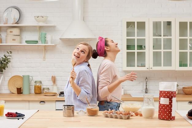 2人の陽気な友人が一緒にデザートを作って歌います Premium写真