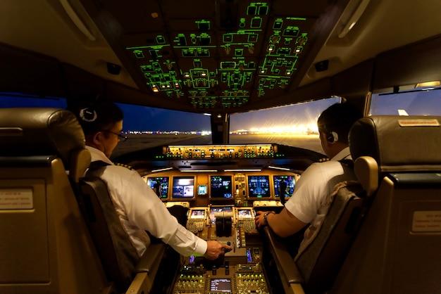 2人の航空会社のパイロットが夜間に飛行機のエンジンを始動させています。 Premium写真