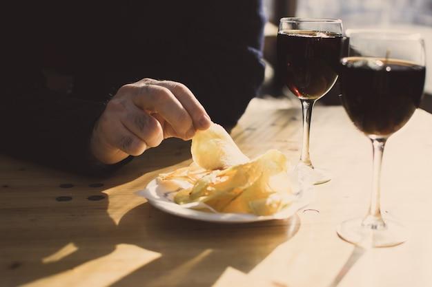 ポテトチップスと2杯の害虫を持つ男の手。スペインの前菜 Premium写真
