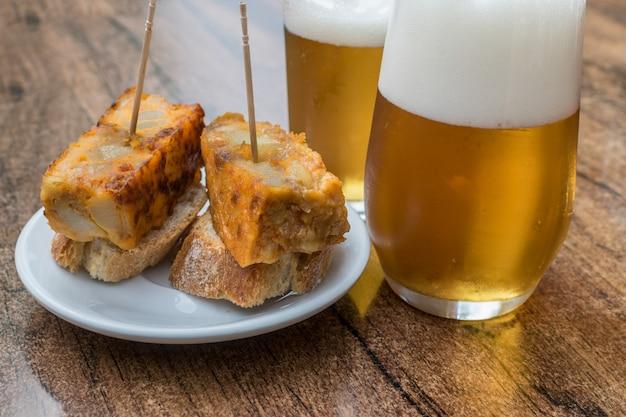 スペインのオムレツと木製のテーブルの上のビールを2杯 Premium写真