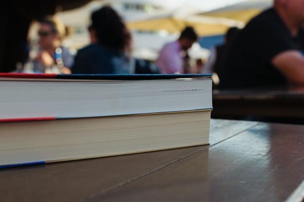 大学のキャンパスのテーブルに2冊の本が積まれています Premium写真