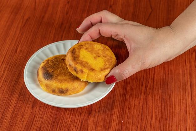 コロンビアとベネズエラで人気の新鮮なホットアレパは、2つのコーンケーキで作られ、それらの間のチーズが溶けるまで揚げられ、食べ物 Premium写真