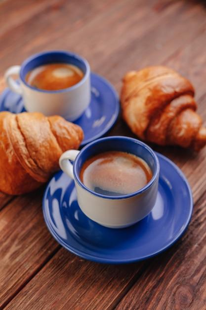 2杯のコーヒーとクロワッサン、木製の背景、良い光、朝の雰囲気 Premium写真