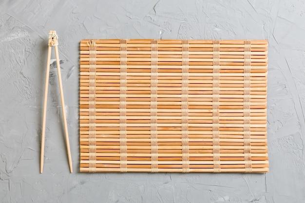 空の竹マットまたは石の上の木の板で2つの寿司トレーニングスティック Premium写真
