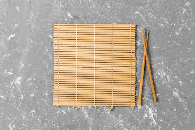 空の茶色の竹マットまたはセメントの背景に木製プレートと2つの寿司箸 Premium写真