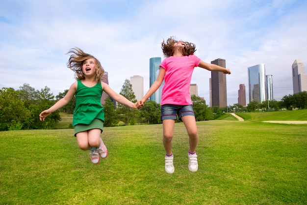 街のスカイラインで幸せな手を握ってジャンプ2人の女の子の友人 Premium写真