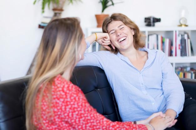 2人の友人が話していると自宅のリビングルームのソファーで笑って Premium写真