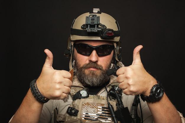 軍の制服を着た残忍な男は2本の指を示しています。 Premium写真