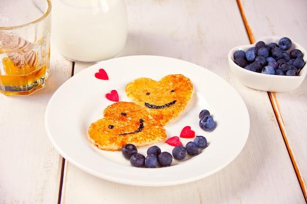 白いテーブルの上の果実とハートの形をした2つのパンケーキのプレート Premium写真