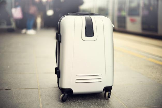2 чемодана стоя на железнодорожном вокзале против поезда города. Premium Фотографии
