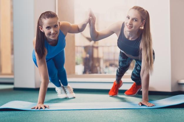 2人の幸せな女の子がトレーニングでスポーツ運動を行います Premium写真