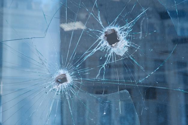 ガラス窓に2つの弾痕 Premium写真
