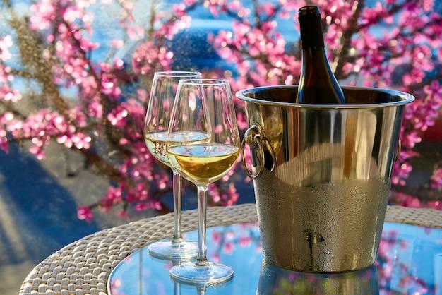 海と花の背景にガラステーブルの上の白の冷たいワインを2杯。 Premium写真