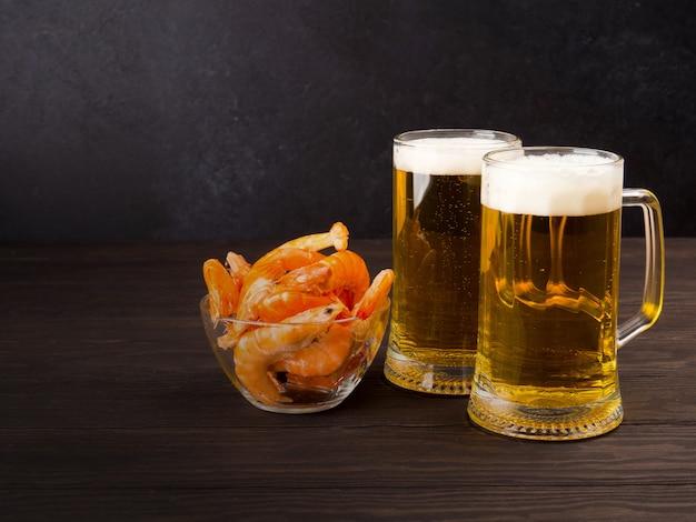 エビと一緒に、黒の上に2杯の軽いビールがあります Premium写真