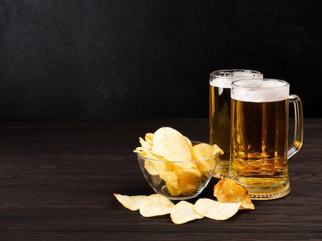 ビールとチップとピーナッツの木の暗い2杯 Premium写真