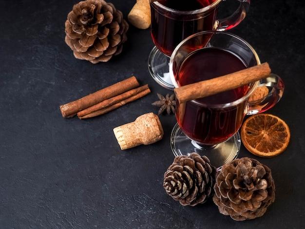 オレンジとスパイスのホットホットワインを2杯とマンダリンと小枝の木。 Premium写真
