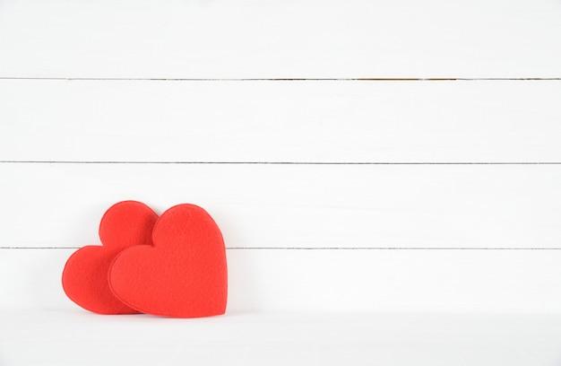 白い木製の背景に2つの赤いハート。愛の概念バレンタイン・デー。ヘルスケアの概念 Premium写真