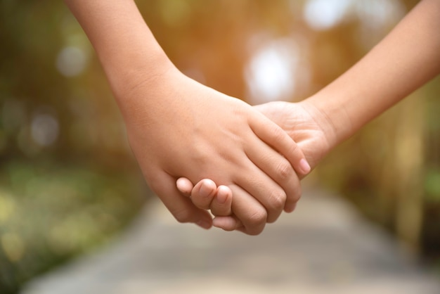 木製の方法で手を取り合って2人の子供 Premium写真