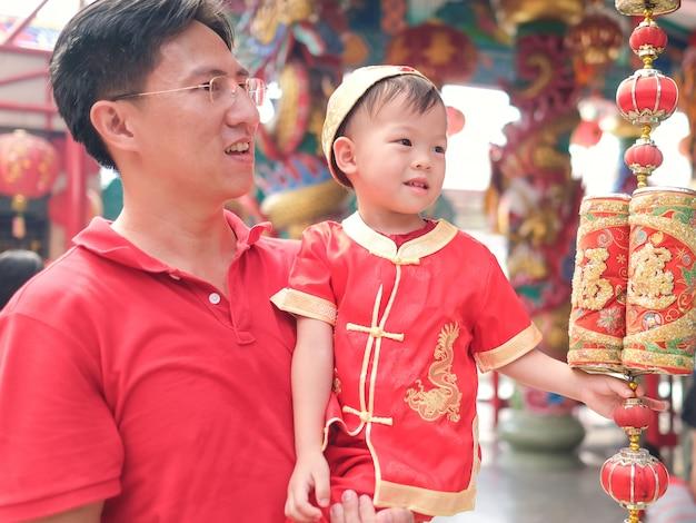 Азиатская семья празднует китайский новый год, милый маленький 2-летний малыш мальчик в традиционном красном китайском костюме в местном китайском храме со своим отцом Premium Фотографии
