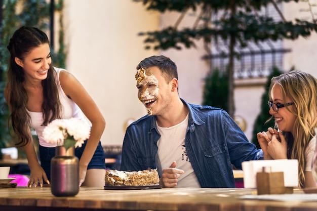 2人の白人の女の子とケーキクリームと顔日焼けを持つ男が笑って、屋外のテーブルの周りに座っています。 無料写真