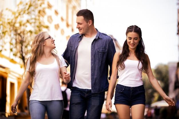 2人の美しい白人の女の子と男の子が通りを歩いています。 無料写真