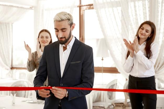 ハンサムなビジネスマンが公式に赤いリボンを切っているとき、2人の女性が手をたたく 無料写真