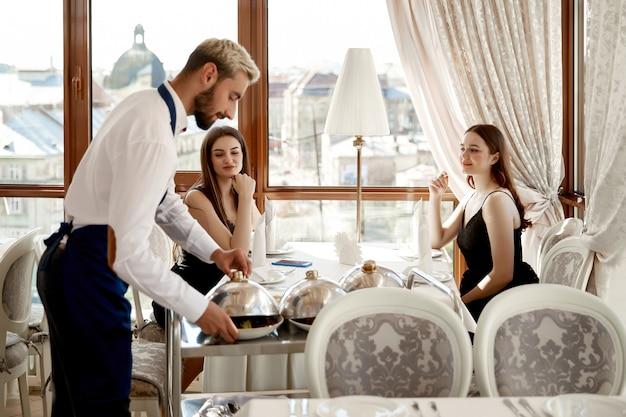 ウェイターはレストランで2人の魅力的な女性に温かい料理を提供しています 無料写真