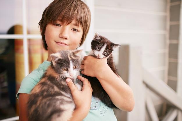 魅力的な小さな男の子は彼の腕の中で2つの子猫を保持します 無料写真