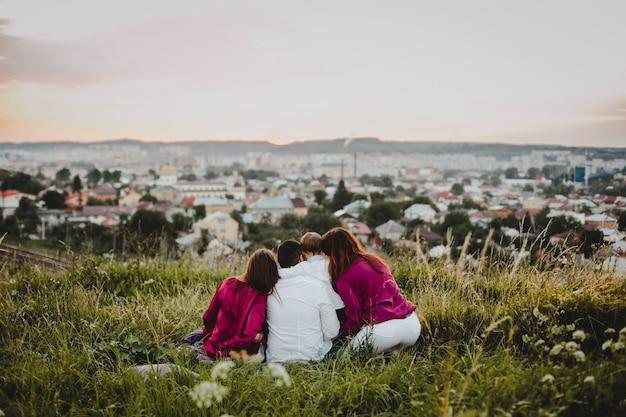 家族写真。男、2人の女性と小さな男の子が芝生の上に座る 無料写真