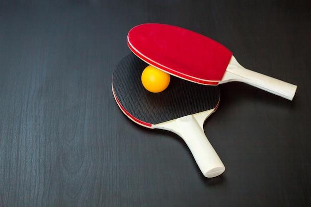 2つの卓球または卓球ラケットと黒の背景にボール Premium写真