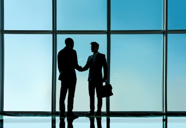 2人の若いビジネスマンが近代的なオフィスに立っています。 Premium写真