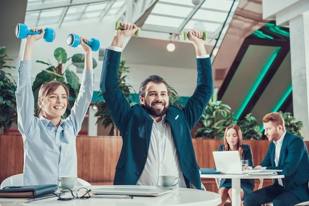 オフィスのデスクでダンベル運動をする2人の労働者。 Premium写真