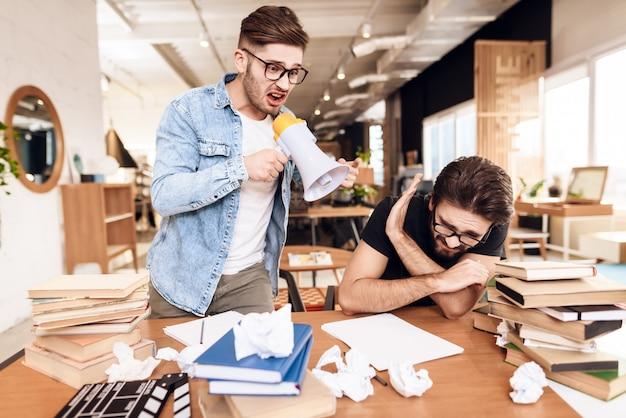 本に囲まれた机で働く2人のフリーランサーの男性。 Premium写真
