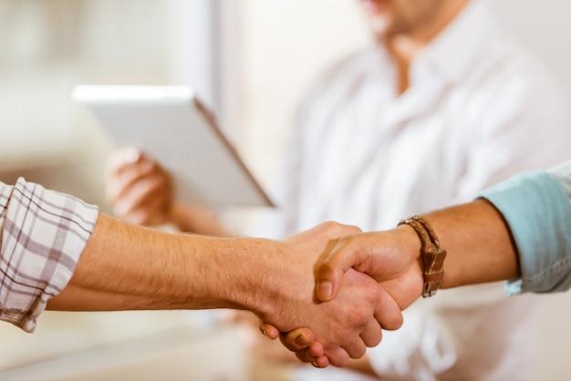 カジュアルな服装の2人の若いビジネスマンの握手。 Premium写真